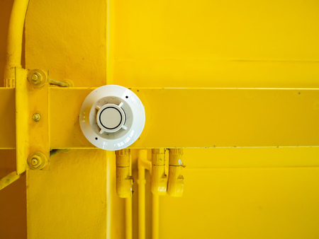 White fire alarm bell attached on yellow ceiling.