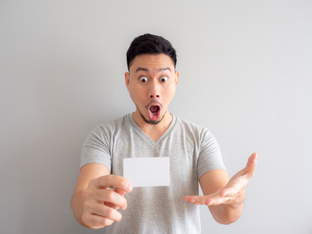 Wow face Asian man is showing a white credit card.