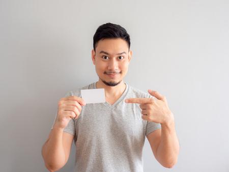 Glücklicher asiatischer Mann zeigt eine weiße Kreditkarte.