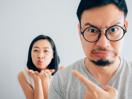 Asian angry and annoyed husband with happy and stubborn wife argument concept.