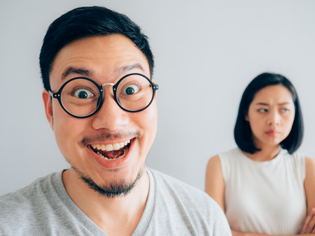 Sly husband with tricky funny face and wife with suspicious face. Stock Photo
