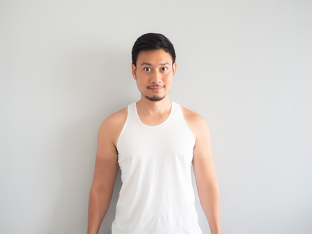 Happy face Asian man in white tank top get tanned on the arm.