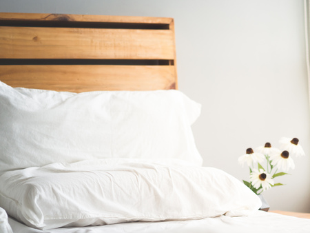 Minimal loft style wooden bed headboard with flowers in morning light. Banque d'images
