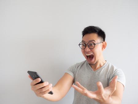 Visage Wow de l'homme asiatique a choqué ce qu'il voit dans le smartphone sur fond gris isolé.