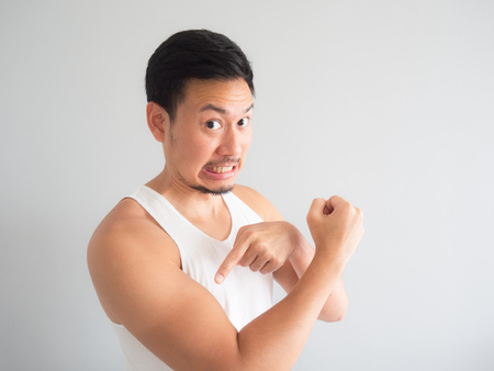 Painful face Asian man in white tank top get sunburn on the arm.