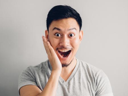 Kopfschussfoto des asiatischen Mannes mit glücklichem Gesicht. auf grauem Hintergrund.