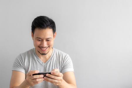 Smile and happy face of Asian man play mobile game. Stock Photo