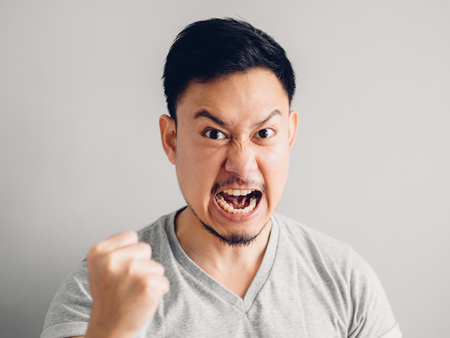 Headshot photo of Asian man with angry and furious face. on grey background. Stock Photo