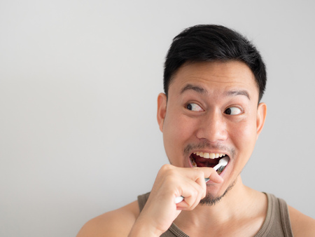 Funny face Asian man brush his teeth without foam. Stockfoto