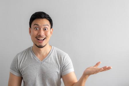 Wow und schockiertes Gesicht des asiatischen Mannes deuten darauf hin, einen leeren Raum des Inhalts zu präsentieren. Werbemodellkonzept.