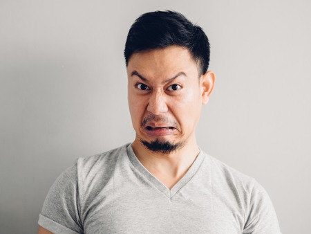Headshot photo of Asian man with hate and disgusting face. on grey background. Фото со стока