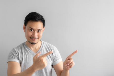 Il sorriso e la faccia felice dell'uomo asiatico indicano di presentare uno spazio vuoto di contenuto. Concetto di modello pubblicitario.