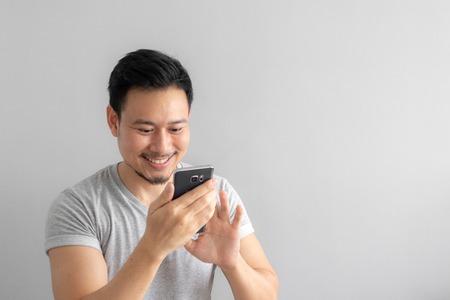 アジアの男性の使用の笑顔と幸せな顔は、彼のスマートフォンを使用して触れます。 写真素材 - 109999615