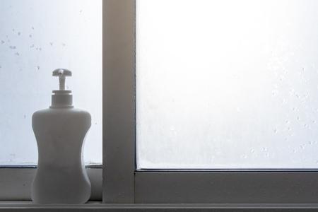 White bottle pump of soap or shampoo on the edge of bathroom windows. Stock Photo
