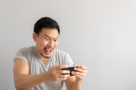 Crazy and funny face of Asian man addicted to play mobile game.