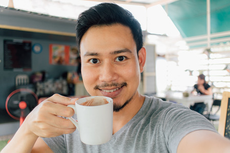 Selfie portrait of happy Asian man drink mug of hot coffee.