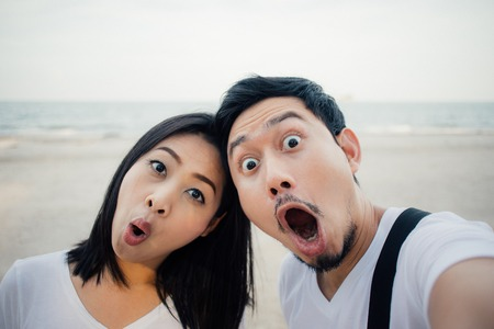 Shocked face of asian couple tourist on romantic beach vacation trip. 免版税图像