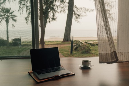 Concept of work and relax. Laptop and hot coffee cup at door step with autumn beach view.