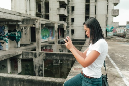 Asian woman enjoy taking photo of an unknown abandoned building. Фото со стока