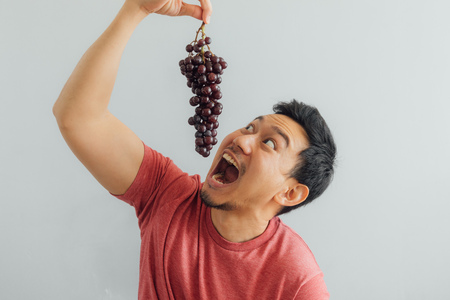 Funny Asian man tries to eat bunch of red grapes. Imagens