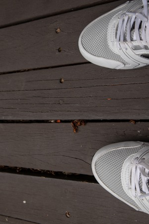 White running shoes on wooden floor. Concept of exercise.