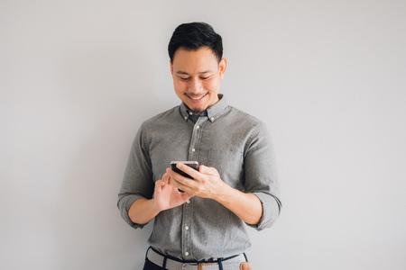 Visage de sourire heureux d'un bel homme asiatique utilise un smartphone. Banque d'images