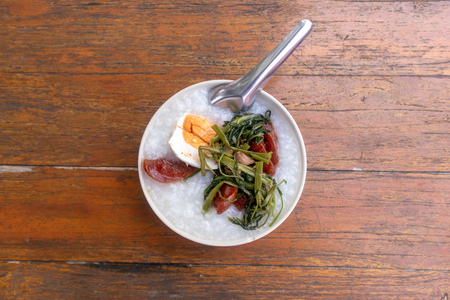 Top view of Thai rice gruel breakfast set served on wooden table.