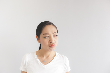 Sulk and grumpy face expression of Asian woman in white t-shirt. Concept of offended peevish and sulky. Stock Photo