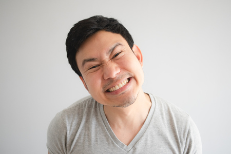 Very happy funny face of Asian man with a big innocent smile in grey t-shirt