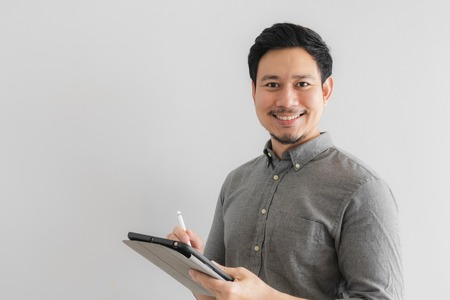 Happy and smile Asian entrepreneur businessman work on his tablet with grey background.
