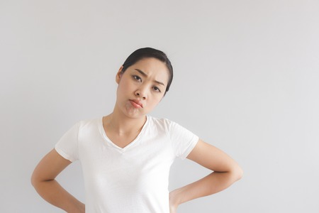 Sulk and grumpy face expression of Asian woman in white t-shirt. Concept of offended peevish and sulky. Standard-Bild