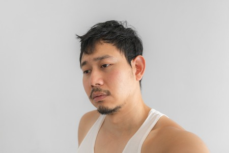 Poor and depressed face of Asian man on grey background. Concept of desperate life. Stock Photo
