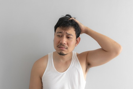 Lazy and messy Asian man in white tank top. Concept of poor and problem. Standard-Bild