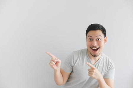 Wow und überraschtes Gesicht des asiatischen Mannes in grauem T-Shirt mit Handpunkt auf leerem Raum.