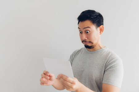 Asian man is shocked and surprised with the white mail message or the bill. Archivio Fotografico