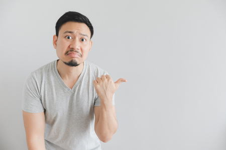 Hate face of Asian man in grey t-shirt with hand point on empty space.