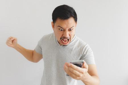 Wütender asiatischer Mann im grauen T-Shirt wird wütend auf das Smartphone.