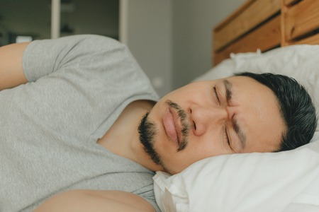 Close up Asian man sleeping on his bed with tortured face. Concept of bad dream.