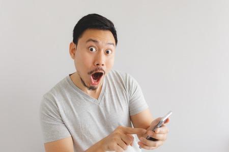 Wow twarz azjatyckiego mężczyzny w szarej koszulce zaskoczona na smartfonie.