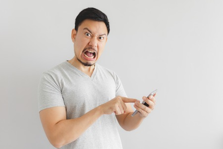 Angry Asian man in grey t-shirt get mad on the smartphone. Imagens - 120840856