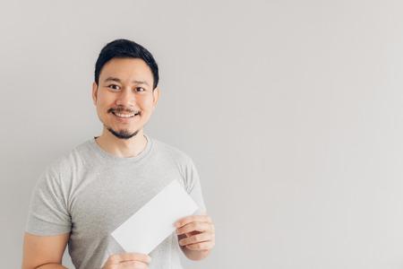 El hombre asiático está contento con el mensaje de correo blanco o la factura.
