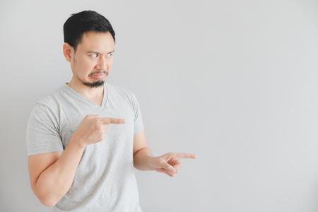 Odio la cara del hombre asiático en camiseta gris con punto de mano en el espacio vacío.