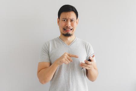 アジアの男は、スマートフォン上で何を示して泣いて悲しい。