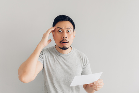 Asian man is shocked and surprised with the white mail message or the bill. Imagens