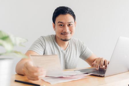 Glücklicher asiatischer Mann hat die Probleme mit Abrechnung und Schulden beseitigt.