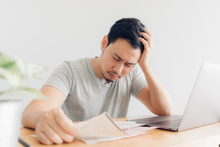 Sad Asian man has problems with billing and debts. Banque d'images