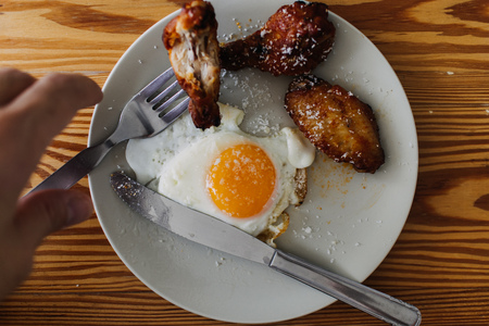 Homemade meal set of fried egg and fried chicken wings. Concept of eating in living room.