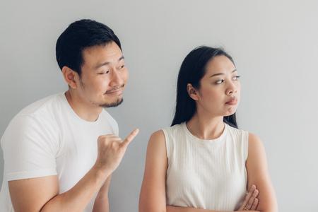 Bouder et réconcilier un couple asiatique amoureux en t-shirt blanc et fond gris. Banque d'images