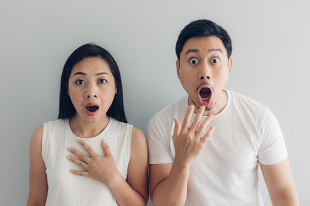 Überraschter und schockierter asiatischer Paarliebhaber im weißen T-Shirt und im grauen Hintergrund.