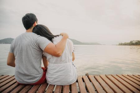 Pareja de amantes asiáticos se mantienen unidos y admiran el hermoso paisaje romántico del lago.